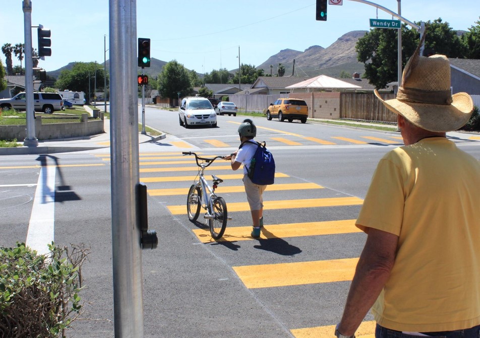 Kid walking bicycle in crosswalk.